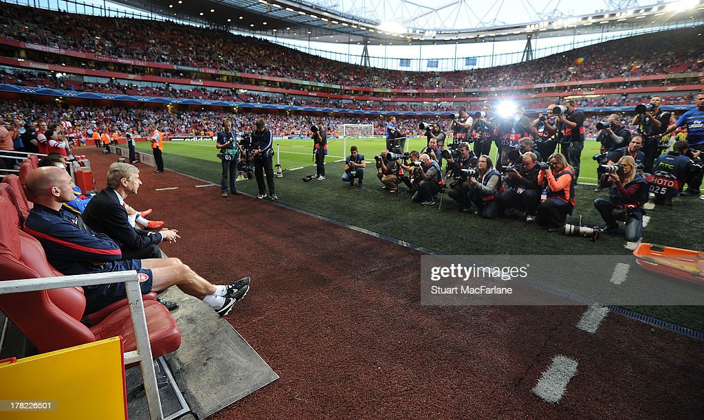 Arsenal manager Arsene Wenger is photographed in the dug out before the UEFA Champions League Play Off Second leg match between Arsenal FC and Fenerbahce SK at Emirates Stadium on August 27, 2013 in London, England.