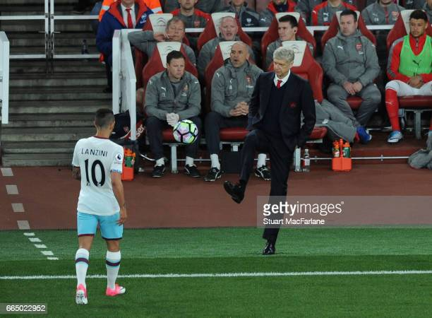 Arsenal manager Arsene Wenger kicks the ball to West Ham's Manuel Lanzini during the Premier League match between Arsenal and West Ham United at...