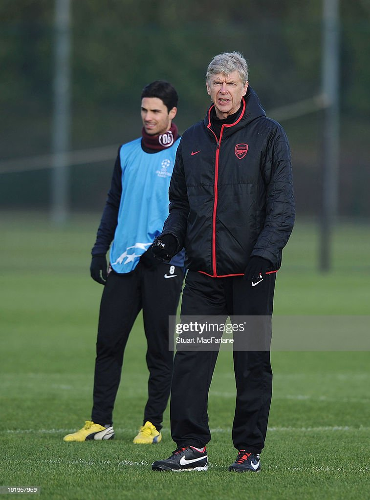 Arsenal manager Arsene Wenger (R) looks on beside Mikel Arteta during a training session ahead of their UEFA Champions League match against FC Bayern Muenchen at London Colney on February 18, 2013 in St Albans, England.