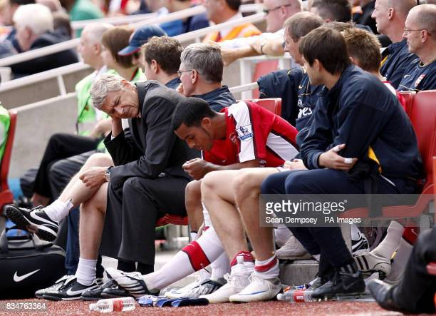 Arsenal manager Arsene Wenger on the bench with Theo Walcott during the Barclays Premier League match at The Emirates Stadium London
