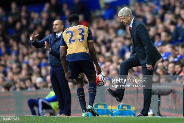 Arsenal manager Arsene Wenger passes the ball to Danny Welbeck as it goes out of play