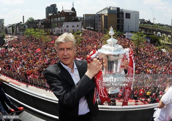 Arsenal manager Arsene Wenger poses with the trophy at the Victory Parade after winning the FA Cup Final on May 18 2014 in London England