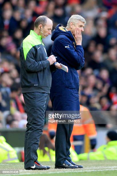 Arsenal manager Arsene Wenger reacts on the touchline as he stands next to fourth official Mike Dean