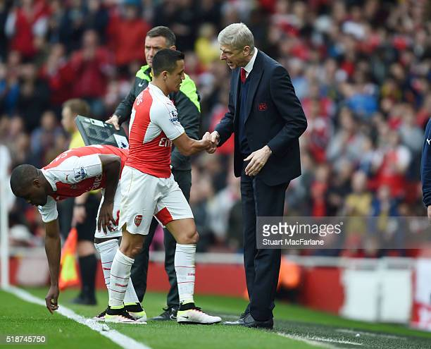 Arsenal manager Arsene Wenger shakes hands with Alexis Sanchez after his substitution during the Barclays Premier League match between Arsenal and...