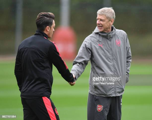 Arsenal manager Arsene Wenger shakes hands with Mesut Ozil before a training session at London Colney on October 18 2017 in St Albans England