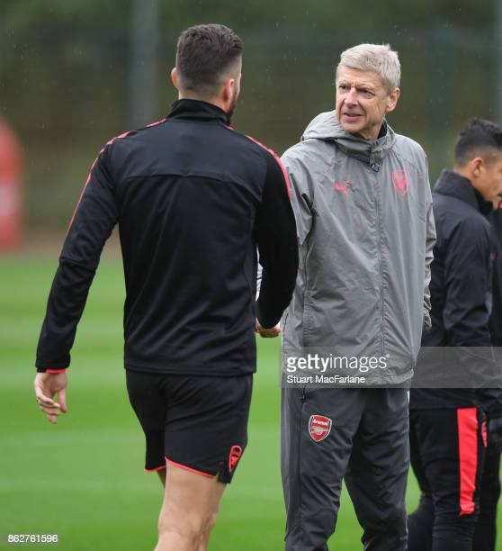 Arsenal manager Arsene Wenger shakes hands with Olivier Giroud before a training session at London Colney on October 18 2017 in St Albans England