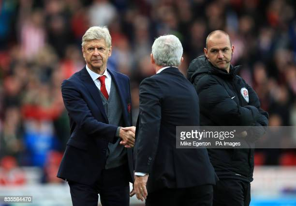 Arsenal manager Arsene Wenger shakes hands with Stoke City manager Mark Hughes after the final whistle during the Premier League match at the bet365...