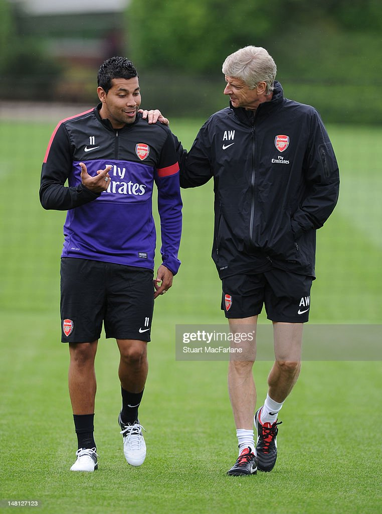 Arsenal manager Arsene Wenger shares a joke with defender Andre Santos during a training session at London Colney on July 10, 2012 in St Albans, England.