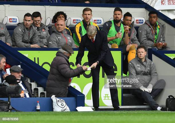 Arsenal manager Arsene Wenger signs an autograph for a West Brom fan during the Premier League match between West Bromwich Albion and Arsenal at The...