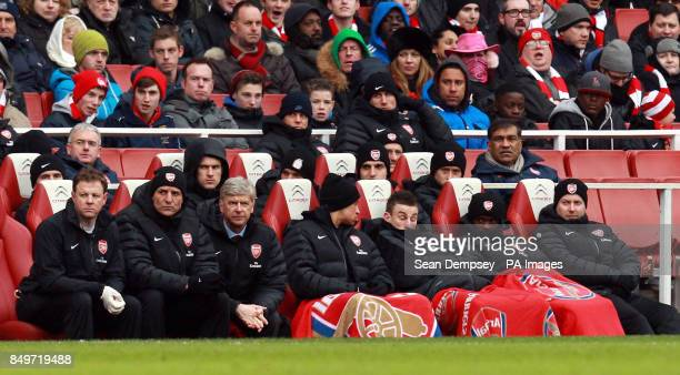 Arsenal manager Arsene Wenger sits with his staff on the bench during the Barclays Premier League match at the Emirates Stadium London