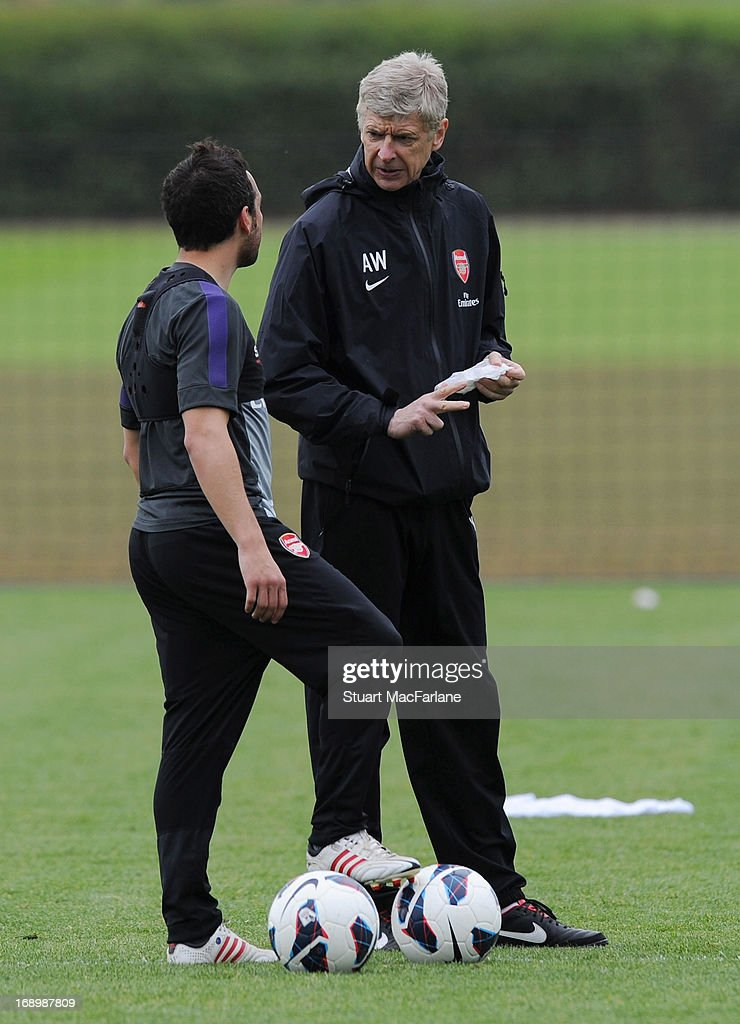 Arsenal manager Arsene Wenger speaks to Santi Cazorla during a training session at London Colney on May 18, 2013 in St Albans, England.