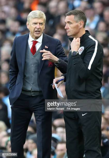 Arsenal manager Arsene Wenger speaks to the fourth official during the Premier League match at the Etihad Stadium Manchester