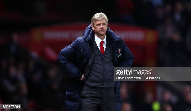 Arsenal manager Arsene Wenger stands hands on hips on the touchline during the Barclays Premier League match at Old Trafford Manchester
