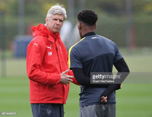 Arsenal manager Arsene Wenger talks to Alex Iwobi before a training session at London Colney on April 22 2017 in St Albans England