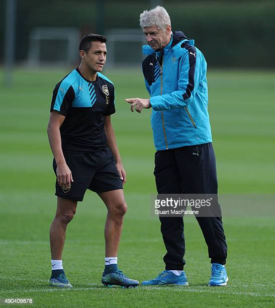 Arsenal manager Arsene Wenger talks to Alexis Sanchez during a training session at London Colney on September 28 2015 in St Albans England