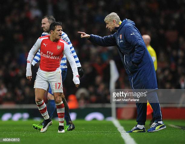 Arsenal manager Arsene Wenger talks to Alexis Sanchez during the Barclays Premier League match between Arsenal and Queens Park Rangers at Emirates...