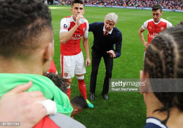 Arsenal manager Arsene Wenger talks to his team before extra time during the Emirates FA Cup SemiFinal match between Arsenal and Manchester City at...