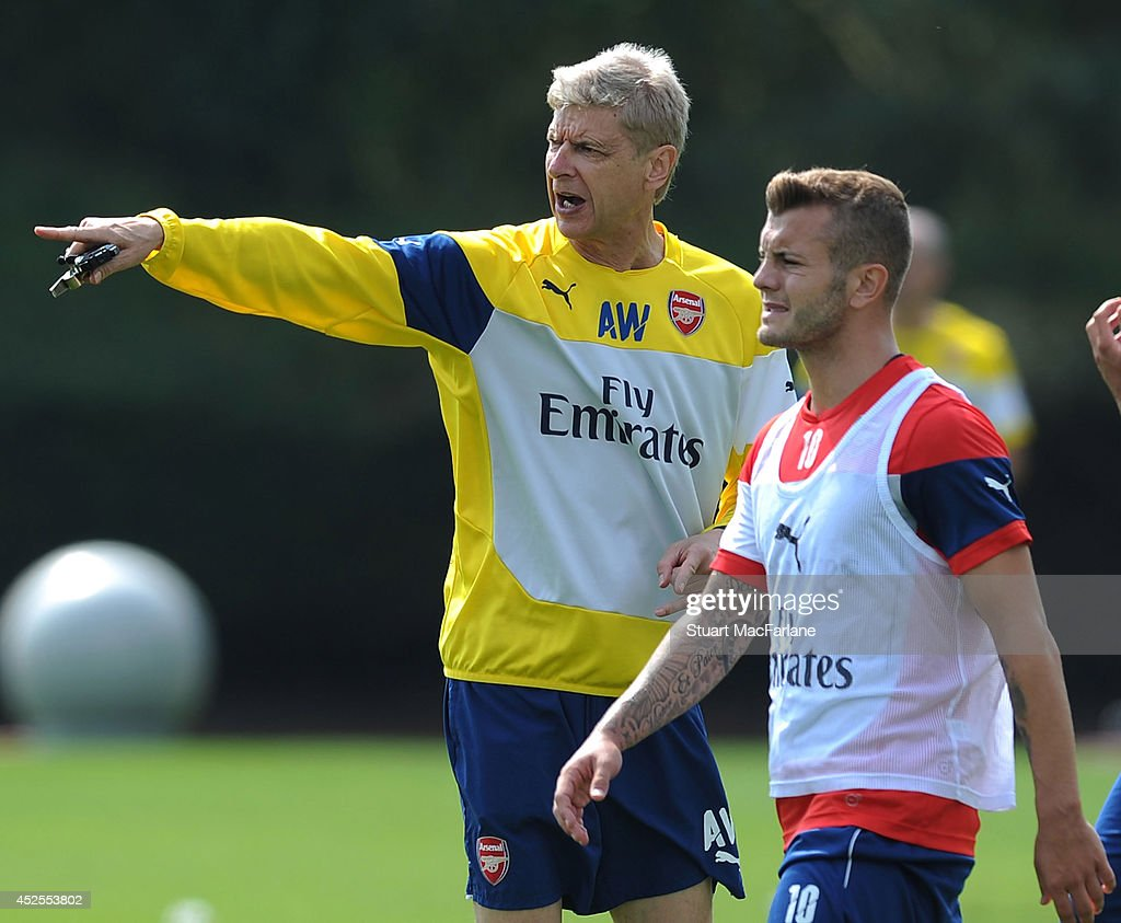 Arsenal manager Arsene Wenger talks to Jack Wilshere during a training session at London Colney on July 23, 2014 in St Albans, England.
