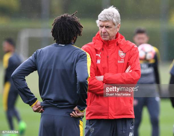 Arsenal manager Arsene Wenger talks to Mohamed Elneny before a training session at London Colney on April 22 2017 in St Albans England