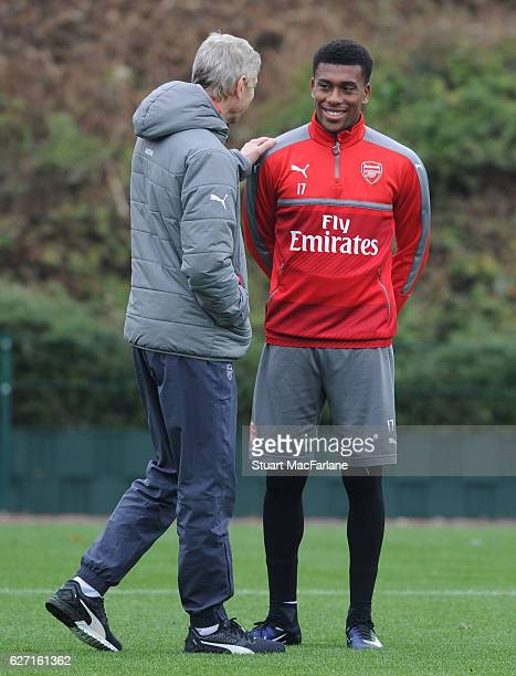 Arsenal manager Arsene Wenger talks with ALex Iwobi during a training session at London Colney on December 2 2016 in St Albans England