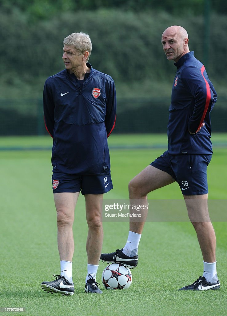Arsenal manager Arsene Wenger talks with assistant Steve Bould during a training session ahead of their UEFA Champions League Play Off second leg match against Fenerbache at London Colney on August 26, 2013 in St Albans, England.