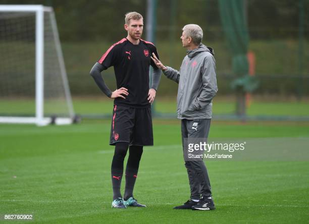 Arsenal manager Arsene Wenger talks with Per Mertesacker during a training session at London Colney on October 18 2017 in St Albans England