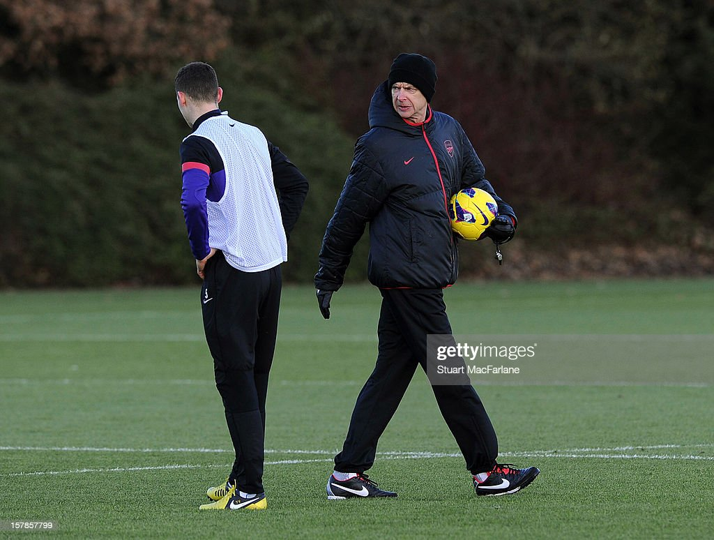 Arsenal manager Arsene Wenger talks with Thomas Vermaelen during a training session at London Colney on December 07, 2012 in St Albans, England.