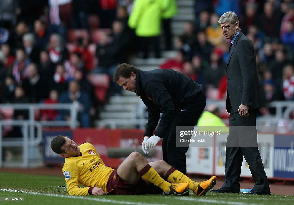 Arsenal Manager Arsene Wenger watches closley as Jack Wilshere of Arsenal is treated on the pitch for an injury after a challenge with Titus Bramble...
