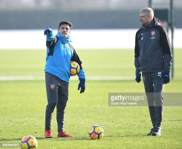 Arsenal manager Arsene Wenger with Alexis Sanchez during a training session at London Colney on December 12 2017 in St Albans England