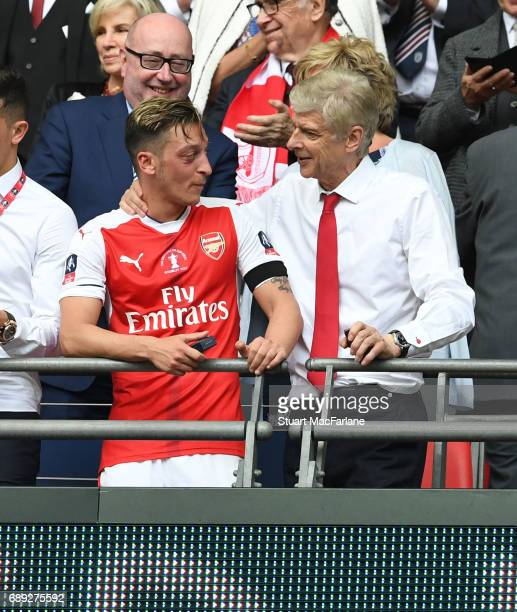 Arsenal manager Arsene Wenger with Mesut Ozil after the Emirates FA Cup Final between Arsenal and Chelsea at Wembley Stadium on May 27 2017 in London...