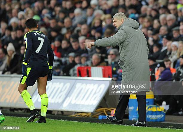 Arsenal manager Arsene Wenger with striker Alexis Sanchez during the Premier League match between Swansea City and Arsenal at Liberty Stadium on...