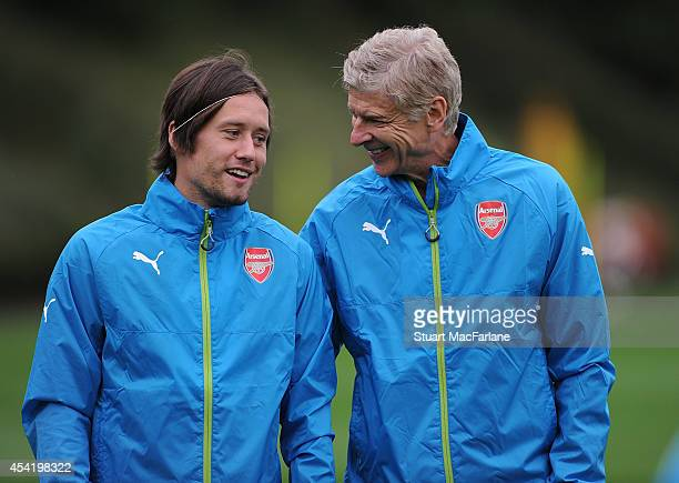 Arsenal manager Arsene Wenger with Tomas Rosicky during a training session at London Colney on August 26 2014 in St Albans England