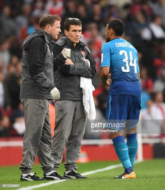 Arsenal physio Colin Lewin and doctor Gary O'Driscoll talk to midfielder Francis Coquelin during the Emirates Cup match between Arsenal and SL...