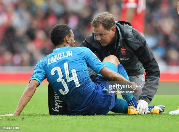 Arsenal physio Colin Lewin treats the injured Francis Coquelin during the Emirates Cup match between Arsenal and SL Benfica at Emirates Stadium on...