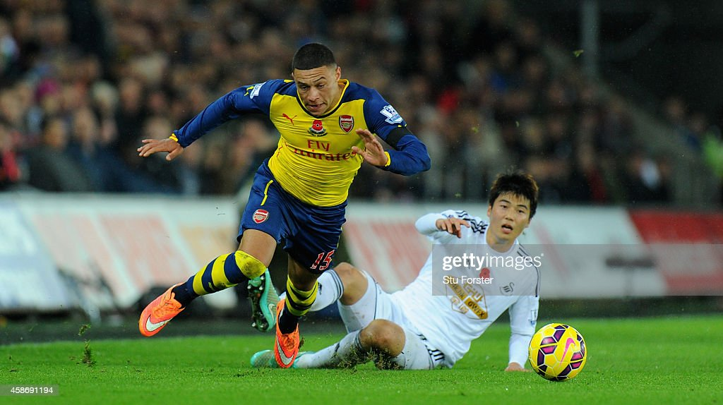 Arsenal player Alex Oxlade-Chamberlin (l) is fouled by Ki Sung-Yueng during the Barclays Premier League match between Swansea City and Arsenal at Liberty Stadium on November 9, 2014 in Swansea, Wales.