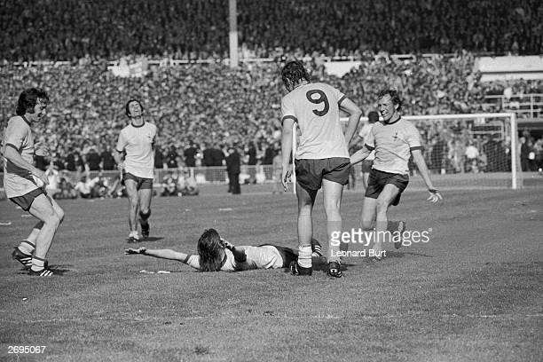 Arsenal player Charlie George lies on the ground and throws his arms in the air after scoring the winning goal during extra time for Arsenal during...
