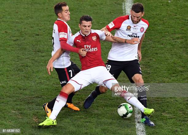 Arsenal player Granit Xhaka is tackled by Western Sydney Wanderers players Steven Lustica and Robert Cornthwaite in their preseason football friendly...