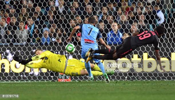 TOPSHOT Arsenal player Joe Willock's shot on goal is blocked by Sydney FC goalkeeper Andrew Redmayne as Michael Zullo looks on in their football...