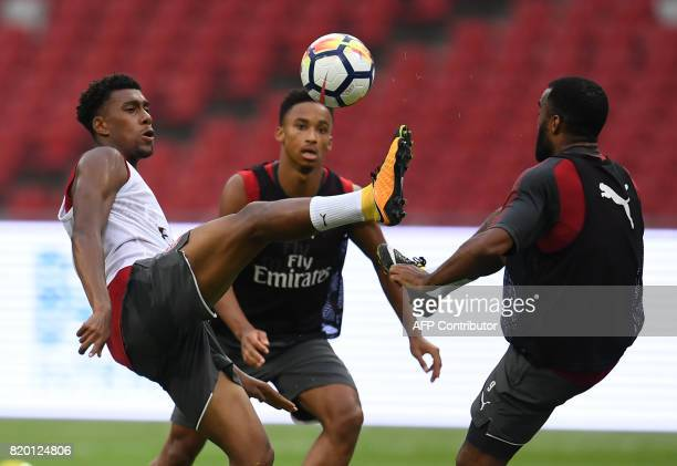 Arsenal players Alex Iwobi and Alexandre Lacazette vie for the ball during a football training session in Beijing's National Stadium known as the...