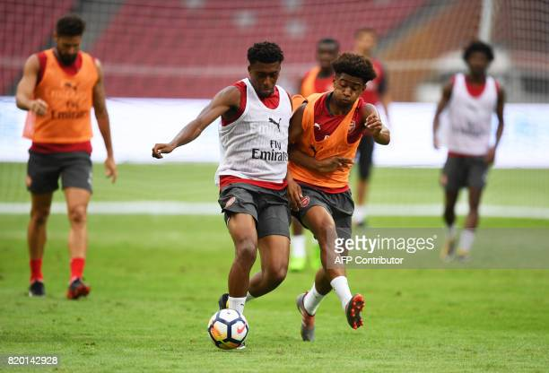 Arsenal players Alex Iwobi and Chuba Akpom vie for the ball during a football training session in Beijing's National Stadium known as the Bird's Nest...