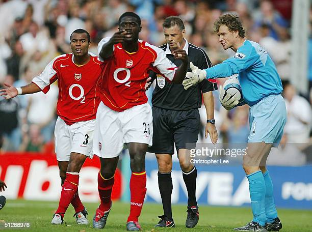 Arsenal players Ashley Cole Kolo Toure and Jens Lehmann argue with referee Mark Halsey over a penalty decision during the Barclays Premiership match...
