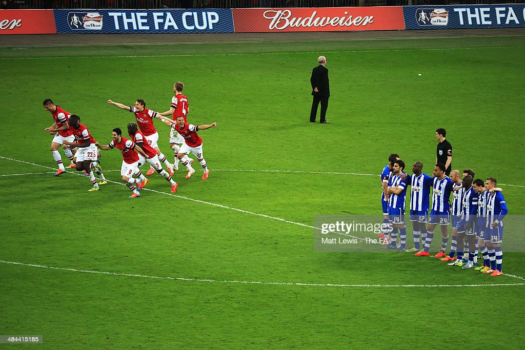 Arsenal players celebrate after winning the penalty shoot-out to claim victory in the FA Cup Semi-Final match between Wigan Athletic and Arsenal at Wembley Stadium on April 12, 2014 in London, England.