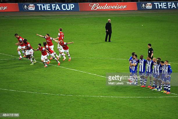 Arsenal players celebrate after winning the penalty shootout to claim victory in the FA Cup SemiFinal match between Wigan Athletic and Arsenal at...