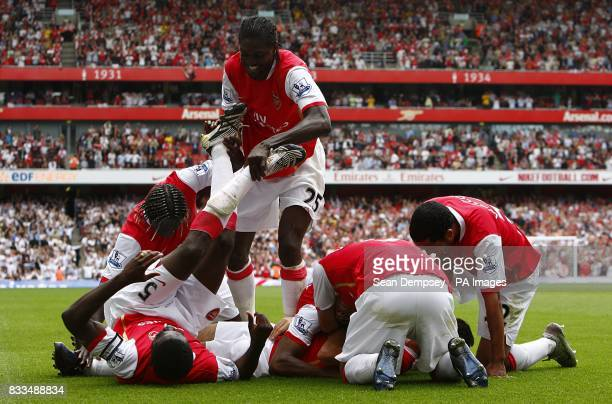 Arsenal players celebrate in a pile after Francesc Fabregas scores the fourth goal of the game