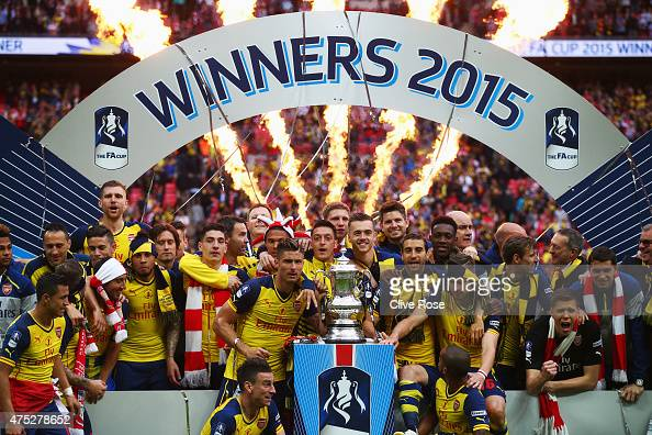 Arsenal players celebrate with the trophy after the FA Cup Final between Aston Villa and Arsenal at Wembley Stadium on May 30 2015 in London England...