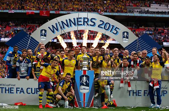 Arsenal players celebrate with the trophy after the FA Cup Final between Aston Villa and Arsenal at Wembley Stadium on May 30 2015 in London England