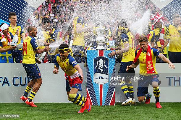 Arsenal players celebrate with the trophy and champagne after the FA Cup Final between Aston Villa and Arsenal at Wembley Stadium on May 30 2015 in...