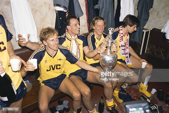 Arsenal players from left Kevin Richardson Steve Bould Paul Merson and Alan Smith celebrate in the dressing room with the League Division One trophy...