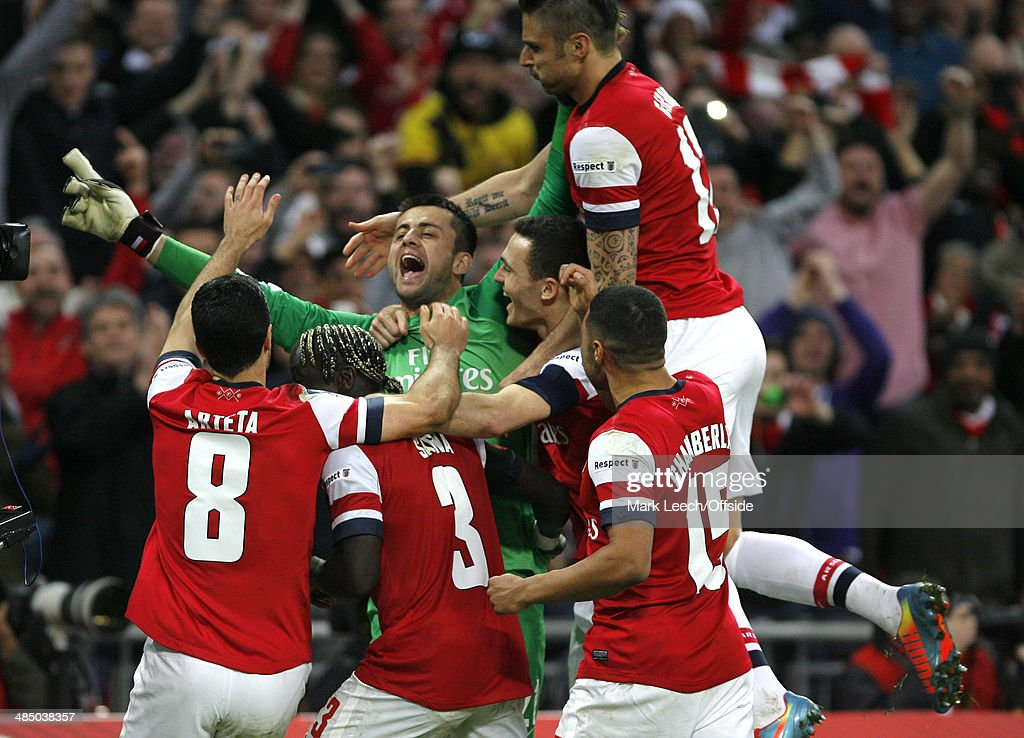 Arsenal players leap on goalkeeper Lukasz Fabianski after his penalty saves in the shoot-out during the FA Cup Semi-Final match between Wigan Athletic and Arsenal at Wembley Stadium on April 12, 2014 in London, England.