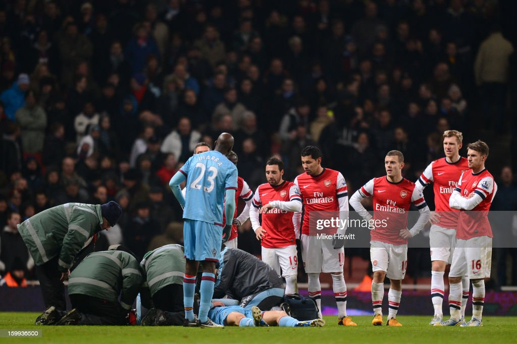Arsenal players look on as Danny Potts of West Ham United receives treatment during the Barclays Premier League match between Arsenal and West Ham United at Emirates Stadium on January 23, 2013 in London, England.